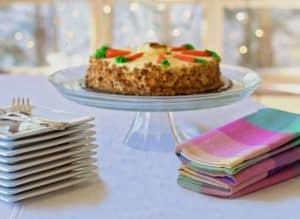 galss cake stand with plates and coloured napkins ready in front