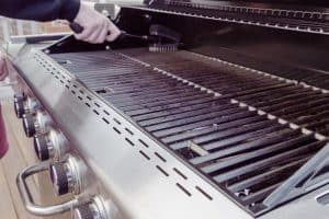 Cleaning gas grill before cooking.