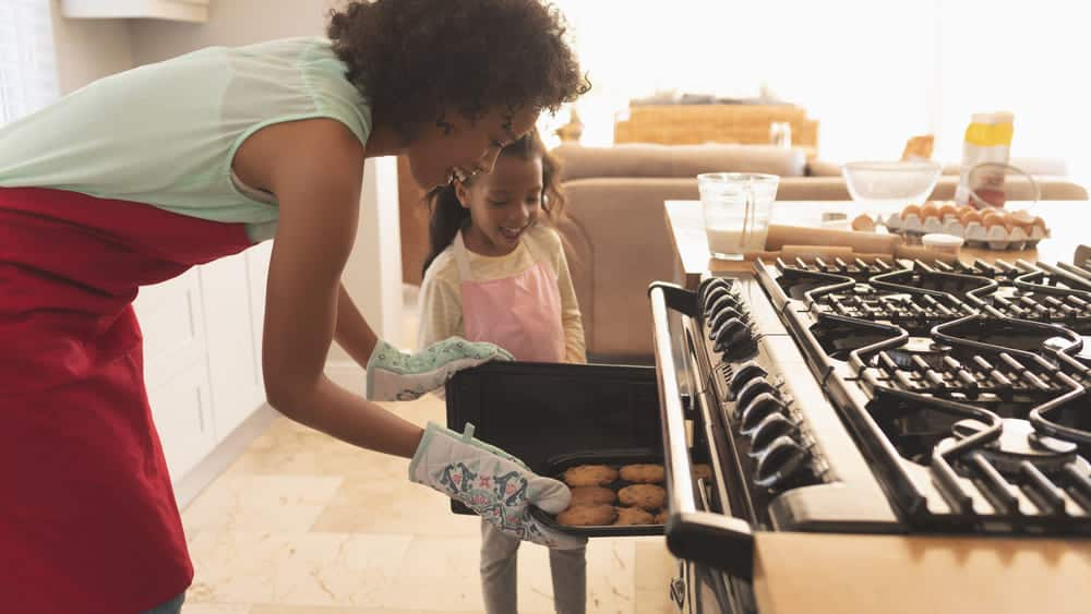 Smart Ovens - woman with daughter pulling cookies out of oven